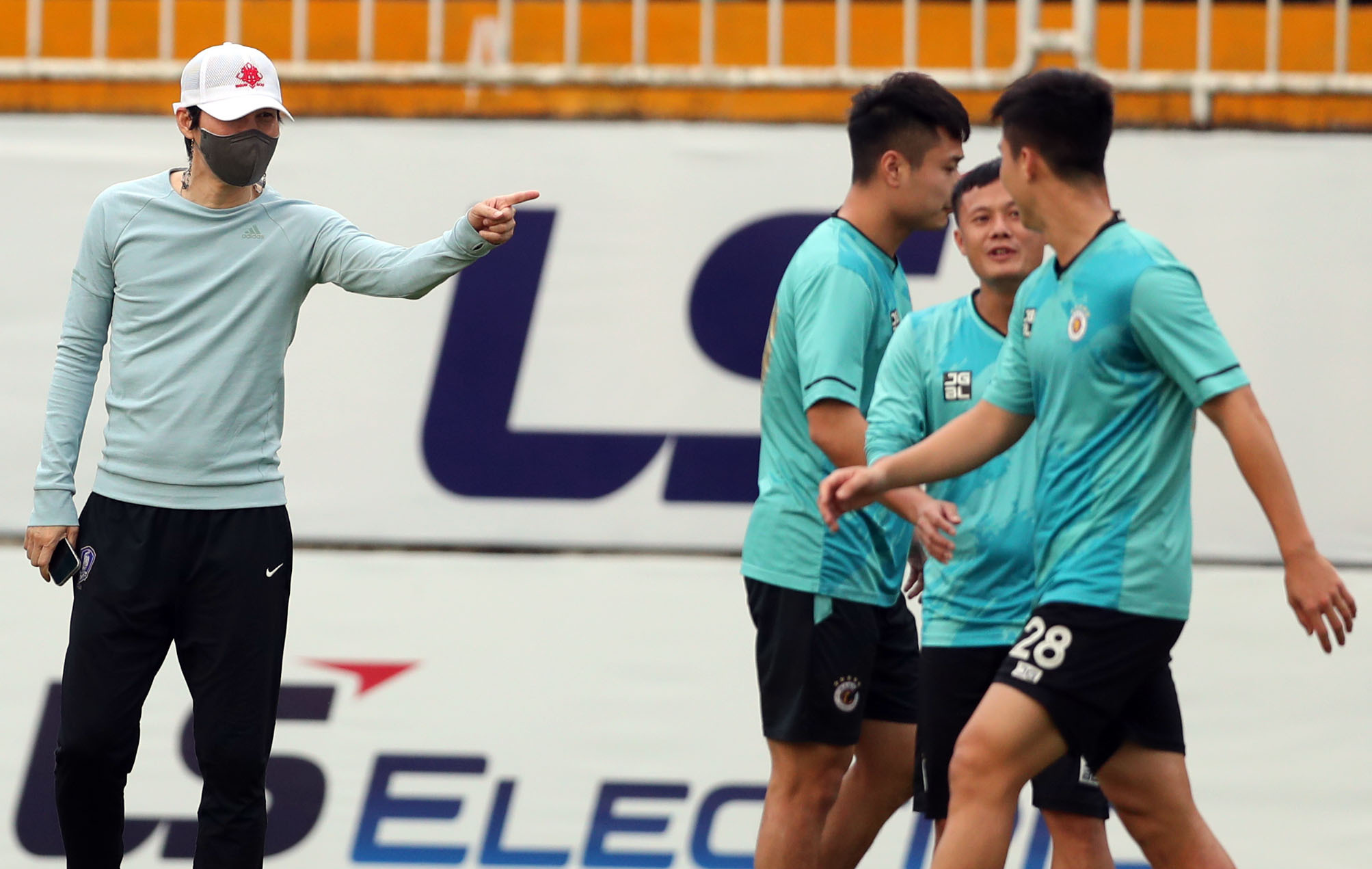 Park Choong-kyun (L) instructs Hanoi FC players during training on April 17, 2021. Photo by VnExpress/Duc Dong.