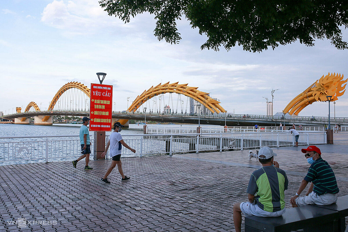 People walk along a park by the iconic Han River in Da Nang City but all wear face masks and keep a distance of one meter.After three weeks without recording new community transmissions, Da Nang City, popular tourism hub in central Vietnam, reopened its public beaches and allowed restaurants and eateries to resume business from Wednesday while locals are also permitted to do morning exercise at public parks.