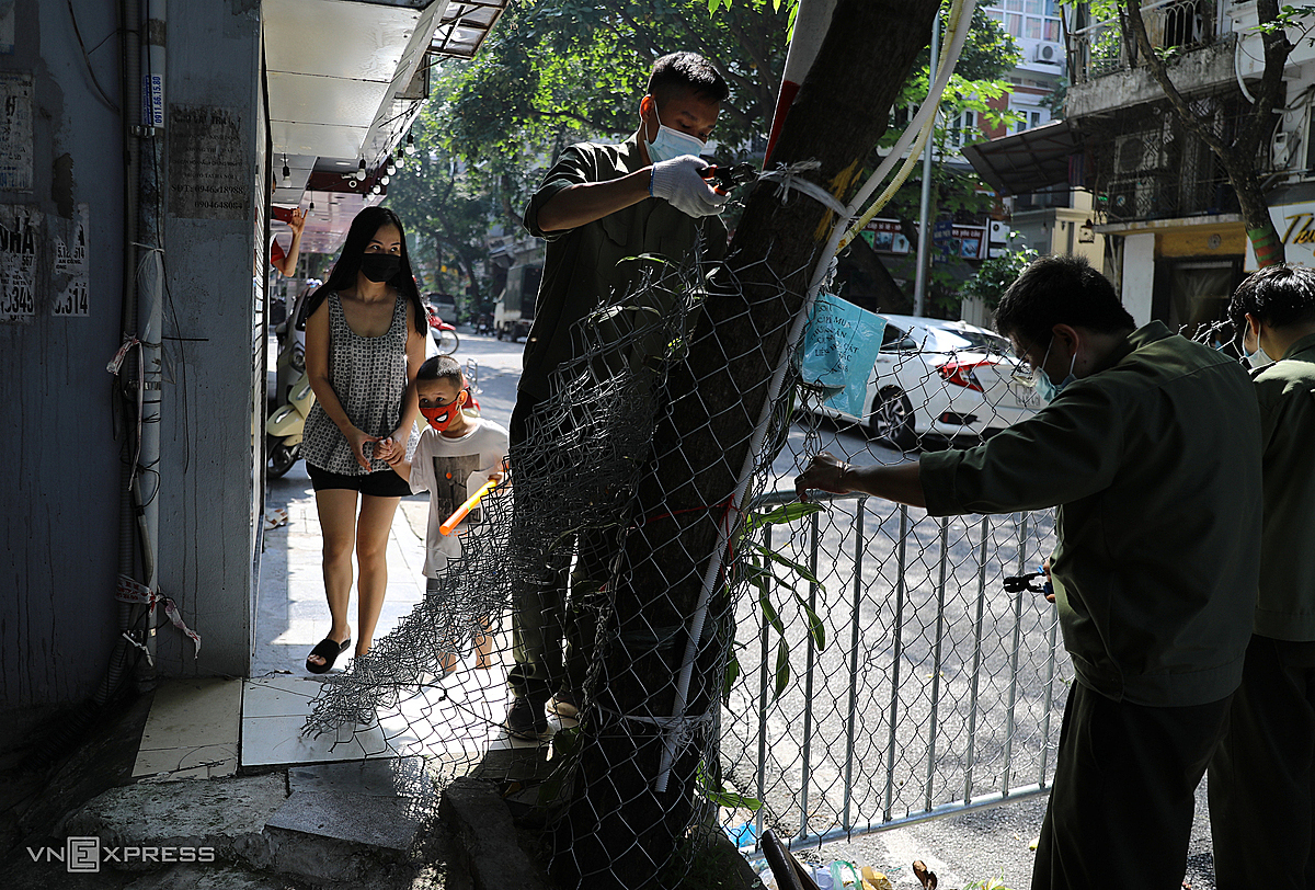 Security force removes barriers on Hanois Cong Duc Street after the city relaxed its coronavirus restrictions, Sept. 21, 2021. Photo by VnExpress/Ngoc Thanh